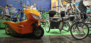 links ein elektrischer Rollstuhltransporter, rechts ein Dreirad mit elektrischem Unterstützungsmotor