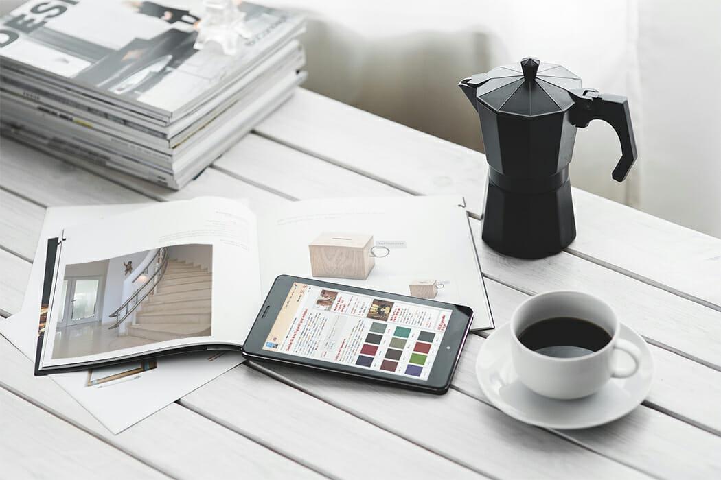 Schreibtisch mit Zeitschriften, Kaffee und Tablet
