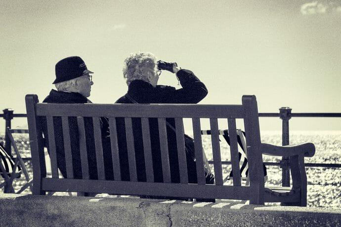 Älteres Ehepaar auf einer Bank blickt auf das Meer