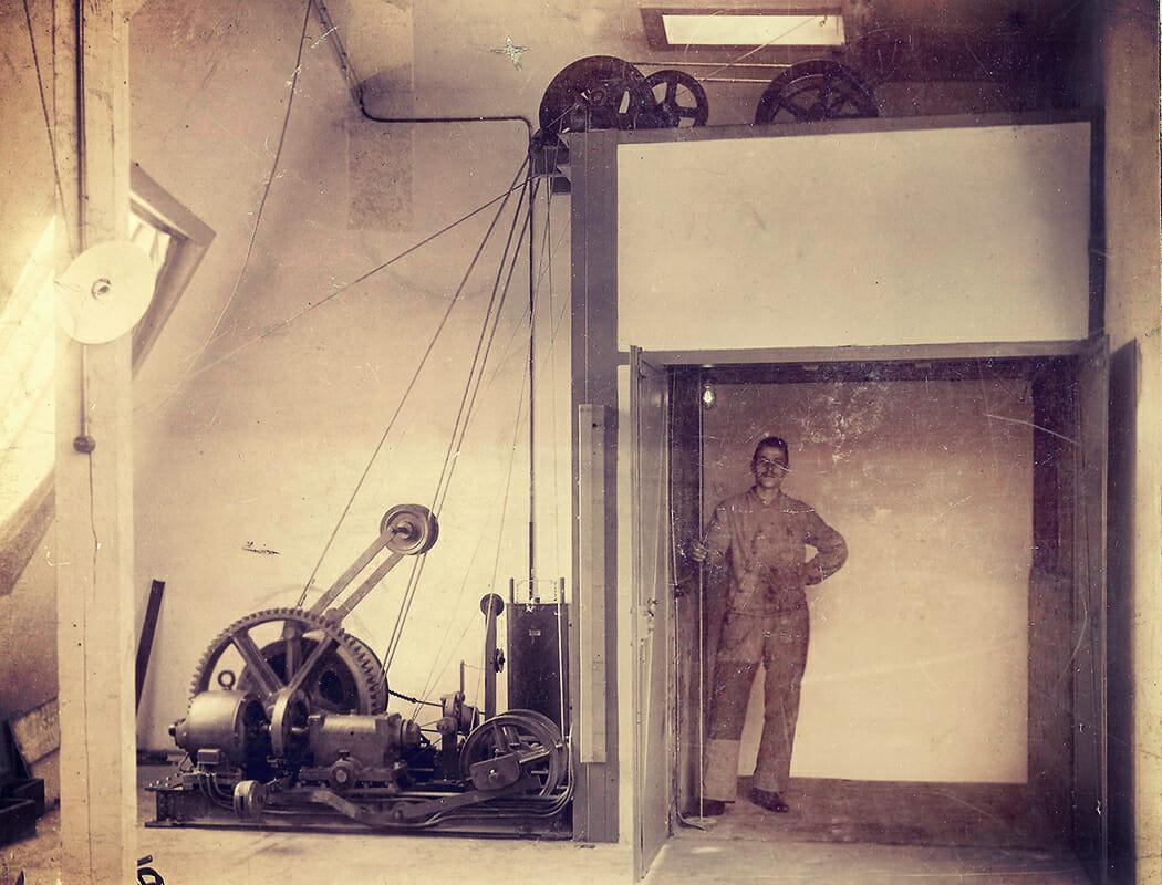 Eine alte Fotografie zeigt einen Aufzugsführer in einer Aufzugskabine ohne Türen