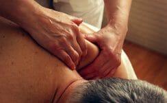 älterer Mann wird bei der Physiotherapie massiert