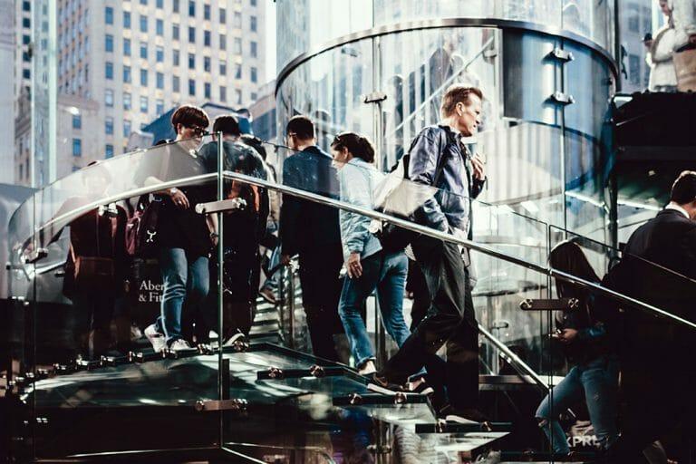 Menschen auf einer Wendeltreppe mit gläsernem Geländer in einem öffentlichen Gebäude
