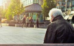 Älterer Mann auf einer Bank in der Stadt
