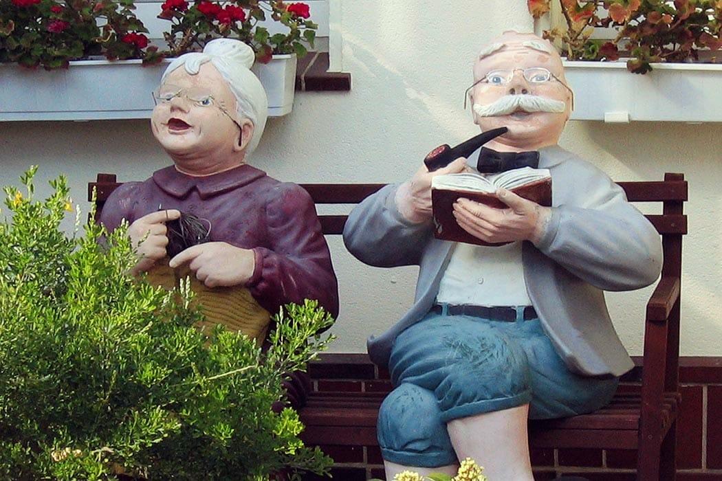 Älteres Ehepaar als Puppen auf einer Bank