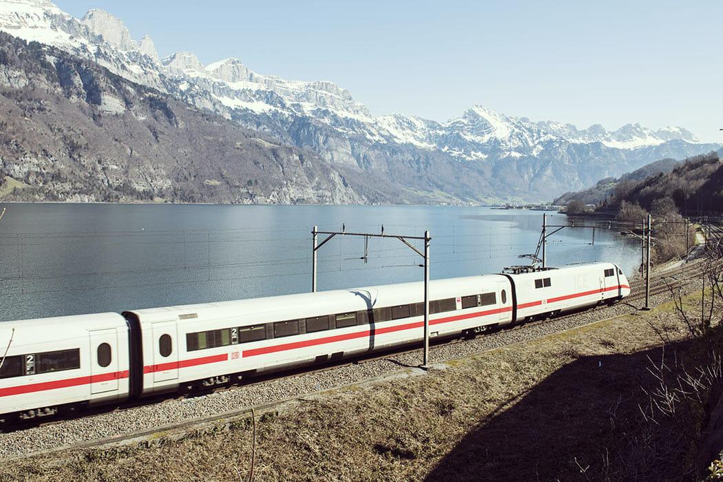 ICE-Zug fährt entlang eines Sees mit Bergen im Hintergrund